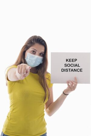 young woman using a surgical mask holding a sign with a message while pointing at the camera on a light background. Safety and awareness concept.
