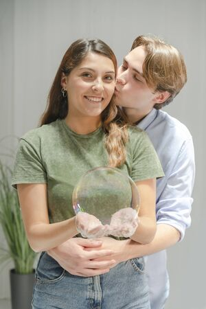 Young beautiful woman smiles and holds a big soap bubble with her hands while being kissed in the cheek by a young man. Couples and fun concept.