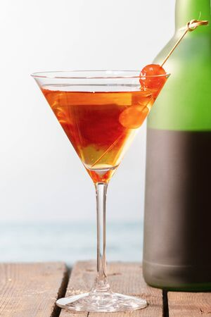 Close up of a homemade cocktail with cherries in a martini glass with a wine bottle behind on a wooden table on an out of focus background. Holiday and leisure concept.
