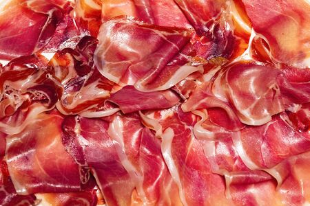 Close up of several delicious thin slices of typical spanish ham. Traditional food and flavor concept.