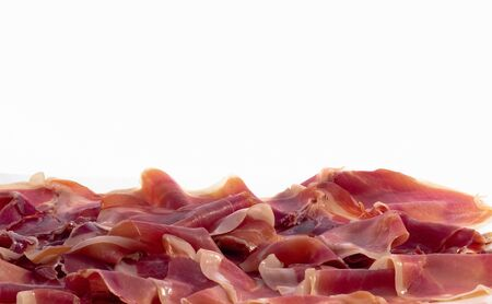 Close up of flavorful and delicious slices of typical spanish ham on a light background. Traditional food and flavor concept. Фото со стока