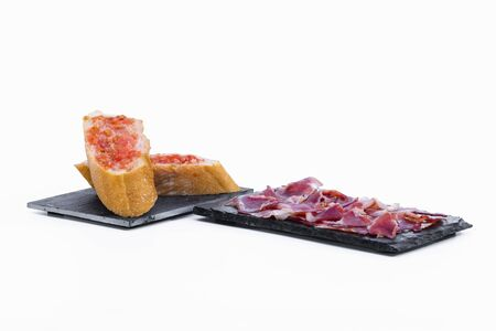 Delicious slices of typical spanish ham on a dark plate next to some tomato-rubbed bread slices on a dark plate on a light background. Traditional food and flavor concept.