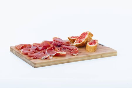 Delicious looking slices of typical spanish ham next to some tomato-rubbed bread slices on a wooden cutting board on a light background. Traditional food and flavor concept.