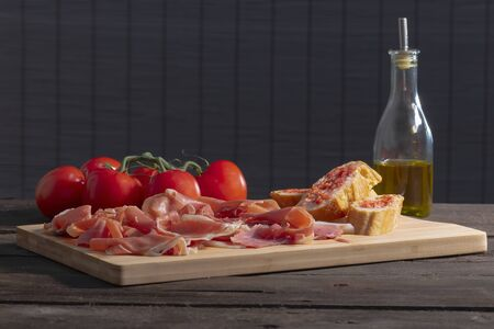 Thin slices of typical spanish ham, tomato-rubbed bread, fresh tomatoes and a glass bottle with olive oil on a wooden table on an out of focus background. Traditional food and flavor concept.