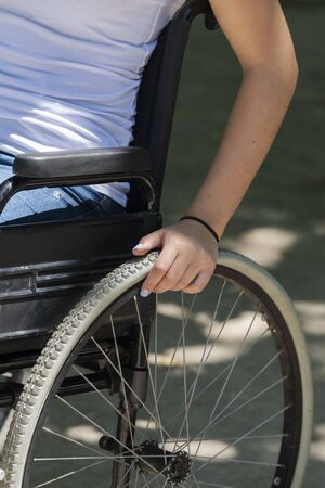 Close up of a female arm handling the wheel of a wheelchair on an out of focus background. Disability and healthcare concept.