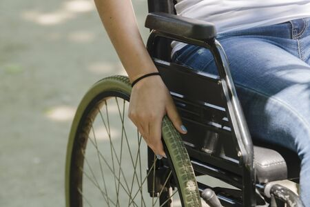 Close up of the wheel of a wheelchair with a female hand resting on it on an out of focus background. Disability and healthcare concept.