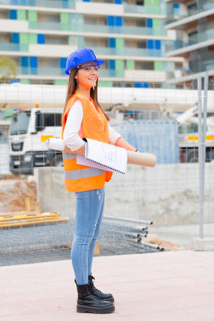 Side view of a beautiful young architecture student wearing safety gear holding blueprints and checking a construction site. Work and apprenticeship concept.