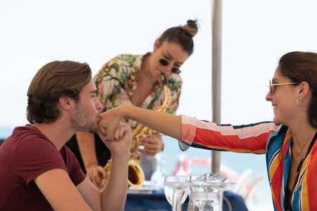 Handsome young man kissing the hand of a beautiful young woman with an out of focus woman playing a saxophone in the back. Romance and street music concept.