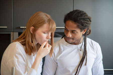 Focused beautiful woman touching her lips while a handsome black man looks at her lovingly on an out of focus background. Diversity and love concept. Stockfoto