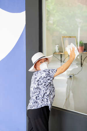 Mature asian woman wearing a face mask and a hat cleaning a glass window while looking at the camera. Safety and work concept.