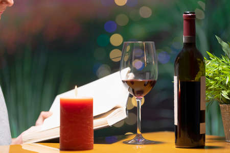 Close up of a glass of wine surrounded by a lit candle and an open bottle of wine, with an open book being held by a person behind on an out of focus background. Leisure and lifestyle concept. Zdjęcie Seryjne