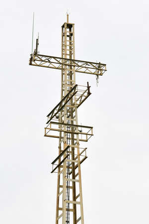 Communications tower on a cloudy sky background