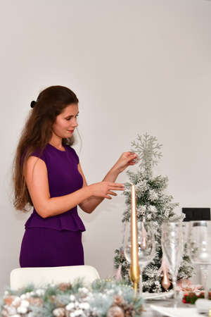 Beautiful woman with a purple dress giving the finishing touches to a Christmas tree. Christmas celebration and decoration concept.