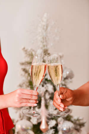Close of of a two female hands doing a toast with champagne glasses with an out of focus Christmas tree at the back. Christmas celebration concept. Archivio Fotografico