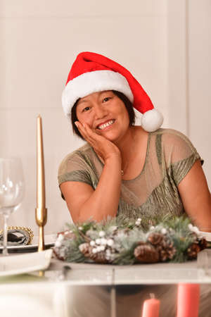 Asian woman sitting at a table with Christmas decorations looking at the camera while drinking champagne. Christmas holiday and decoration concept. Archivio Fotografico