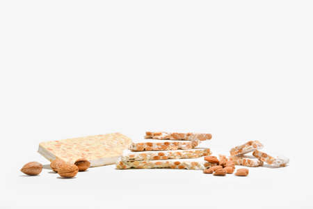 Delicious almond nougat slabs with an assortment of unpeeled almonds and almonds in their shells on a light background. Traditional sweets concept.
