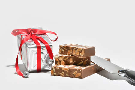 Close up of delicious looking chocolate and almonds nougat with a silver wrapped gift box and a kitchen knife. Traditional sweets and gifts concept. 版權商用圖片
