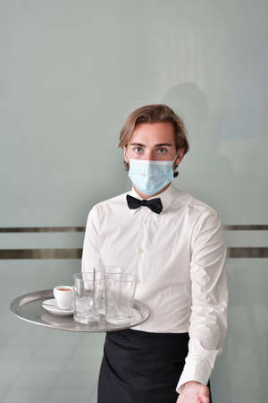 male waiter using a surgical mask holding a bar tray with a cup of coffee and glasses while looking at the camera. Serving and safety concept.