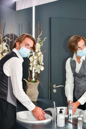 Young male wearing a surgical mask and a receptionist uniform looking at the camera while washing his hands. Hygiene and safety concept. Stockfoto