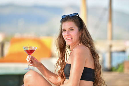 view of a beautiful woman holding a tempting cocktail and looking at the camera on an out of focus background. Leisure and lifestyle concept.