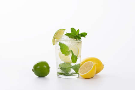 Close up of a tempting glass of mojito cocktail with fresh lemons and a lime on a light background. Alcohol and lifestyle concept.