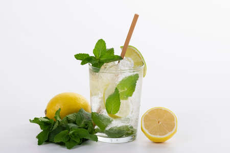 Close up of a refreshing mojito cocktail with a straw surrounded by lemons and fresh mint leaves on a light background. Relax and leisure concept.