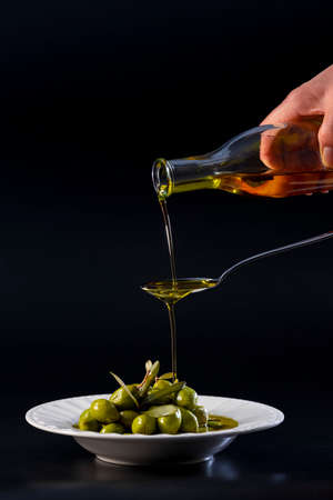 Pure olive oil pouring on a metal spoon and overflowing into a plate with tempting olives on a dark background. Healthy food and abstract concept.