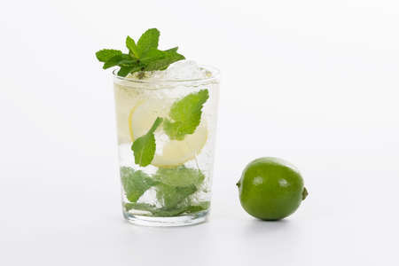 Selective focus of a refreshing glass of mojito cocktail next to a fresh lime on a light background. Alcohol and lifestyle concept.