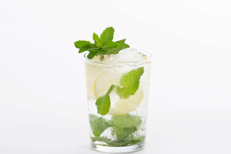 Selective focus and close up of an appetizing looking mojito cocktail on a light background. Alcohol and lifestyle concept.