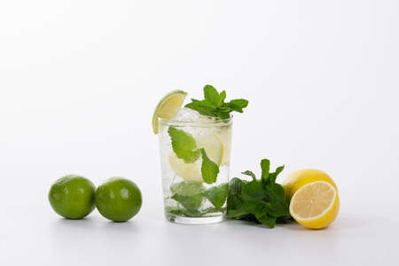 view of a refreshing mojito cocktail surrounded by limes, lemons and fresh mint leaves