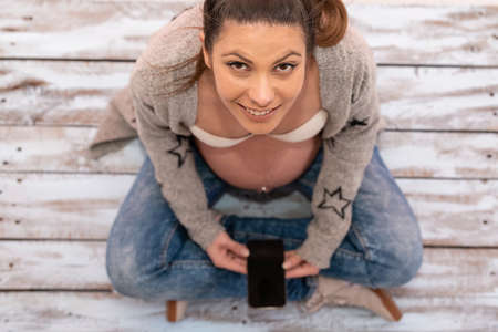 a pregnant woman holding a mobile phone