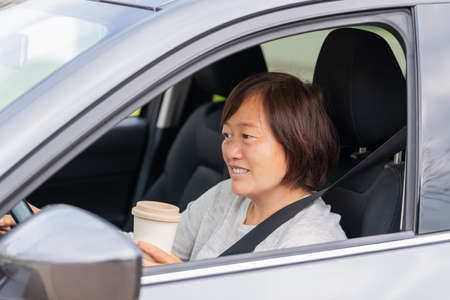 A mature asian woman in a car holding a paper cup: Selective focus. Lifestyle concept.
