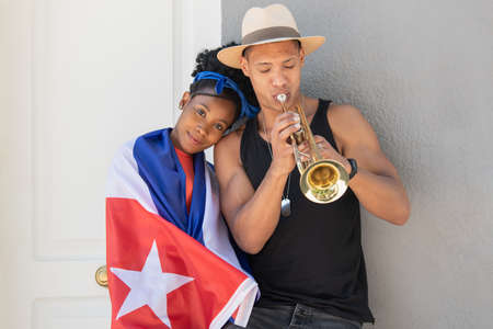 Smiling latina woman leaning on latino man playing the trumpet Stock Photo