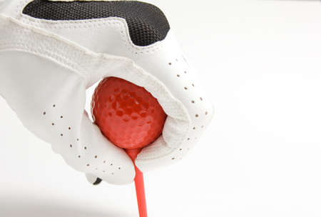 Golf glove by placing a ball on the red tee Stock Photo - 10893806