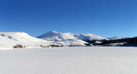 frozen lake: Snowy mountains and frozen lake in winter, Auvergne, in France.