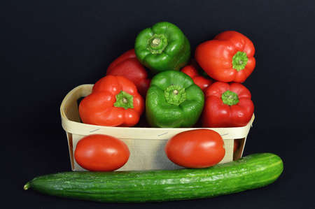market gardener: A pepper assortment in a basket, with tomato and cucumber.