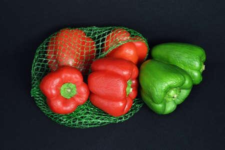 market gardener: A pepper assortment in a net. Stock Photo