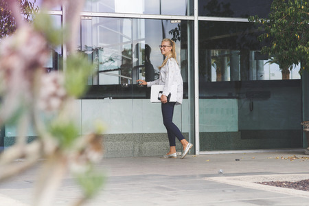 Young woman holding a white laptop entering a building