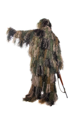 Ghillie suit. Hunter with a rifle dressed in a ghillie suit.