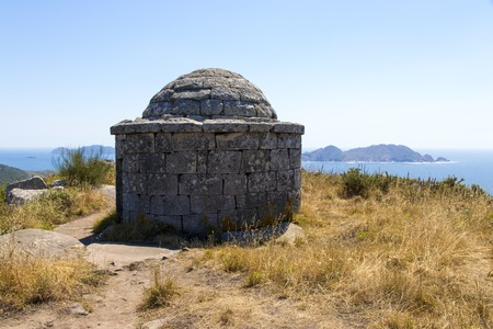 do: The Facho of Donon, an ancient stone lighthouse for guiding sailors in Monte do Facho, Cangas, Galicia, Spain, with the Cies Islands in the background