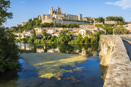 Vistas al atardecer de la ciudad francesa de Beziers, con árboles, el río Orb, y la Catedral del siglo XIII de Saint Nazaire en el fondo Foto de archivo - 84908019