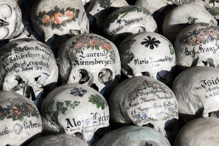 Skulls painted with names, colorful flowers and crosses in the Charnel House or Beinhaus, Hallstatt, Austria Stock Photo
