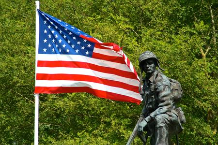 Bronzen beeld van een ijzeren Mike, een soldaat van het Amerikaanse leger met een pistool met een vlag van de Verenigde Staten van Amerika. De Brug van La Fiere, sainte-Mere-Eglise, Normandië, Frankrijk