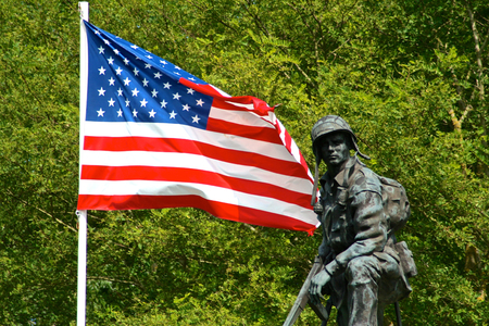 Bronze statue of an Iron Mike, a soldier of the American Army holding a gun with a flag of the United States of America. La Fiere Bridge, Sainte-Mere-Eglise, Normandy, France