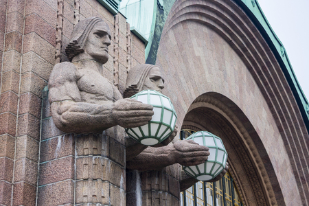 Statues with spherical lamps at Helsinki Central Station (Helsingin paarautatieasema), main station for commuter rail and long-distance trains departing from Helsinki, Finland Editorial