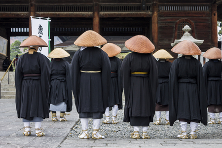 Buddhist monks looking at the Sanmon Gate in Zenko-ji, a buddhist temple located in Nagano, Japan