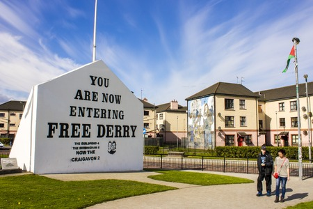 The 'You are Now Entering Free Derry' Corner in Londonderry, Northern Ireland, with two passersby Stock Photo - 94951339