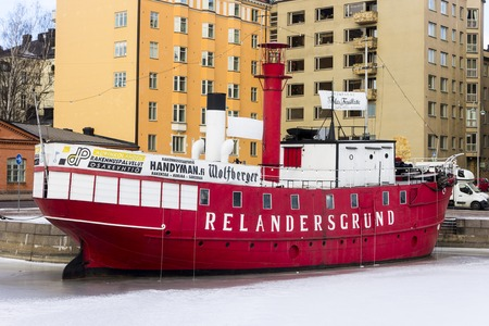 The Majakkalaiva Relandersgrund, a former Finnish lightship (a ship which acts as a lighthouse) painted red that now serves as a restaurant in Helsinki, Finland, surrounded by ice and snow