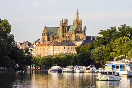 Metz Cathedral seen from afar from the Plan dEau, with the boats of the Port du quai des Regates in the foreground Stock Photo