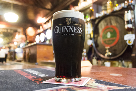 A pint of Irish dry stout Guinness over the counter of The House of McDonnell, a traditional pub in Ballycastle, County Antrim, Northern Ireland
